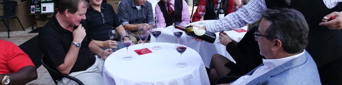 Wine owners celebrating at a round table with a white cloth on it.